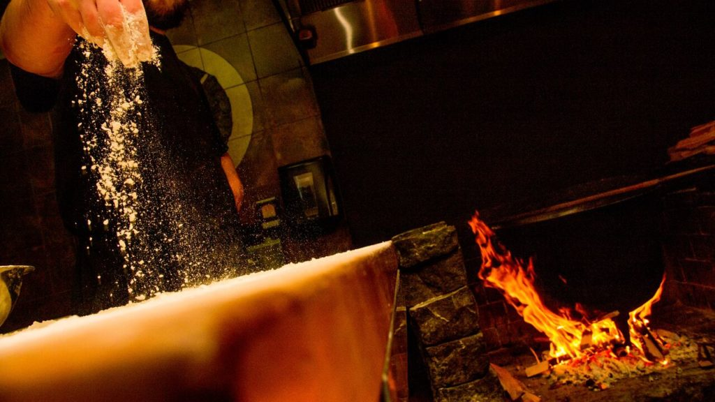 Pizza prepping by the wood fire oven at Creekbread, Whistler.